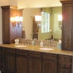 Three XXX sconces line the full mirror in a vanity that provides plenty of storage.